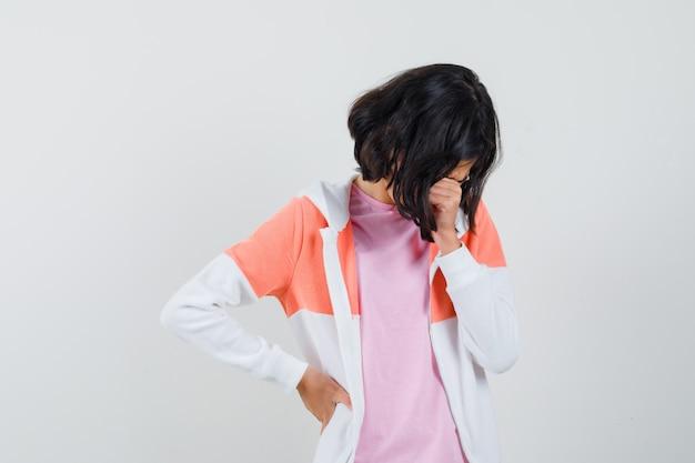 Jeune femme pleurant en veste, chemise rose et l'air troublée.