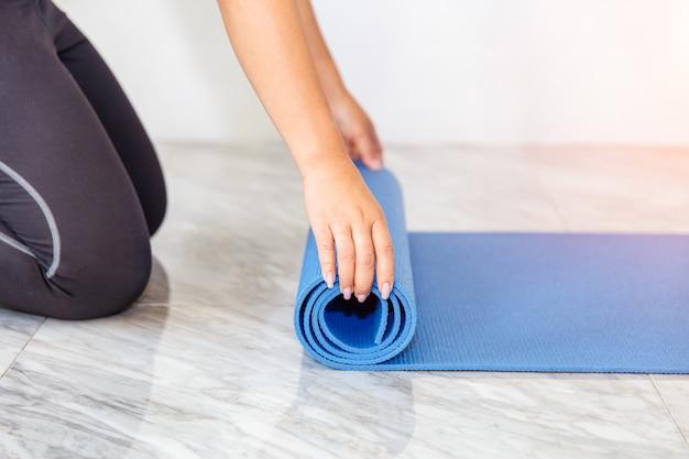 Jeune femme pliant un tapis de yoga ou de fitness bleu après avoir travaillé à la maison