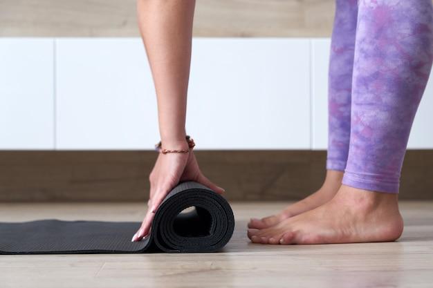 Jeune femme pliant un tapis de yoga ou de fitness noir après avoir travaillé à la maison dans le salon une vie saine