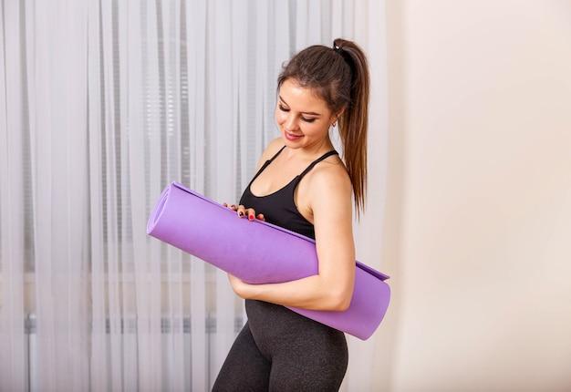 Jeune femme pliant un tapis de yoga ou de fitness violet après l'entraînement