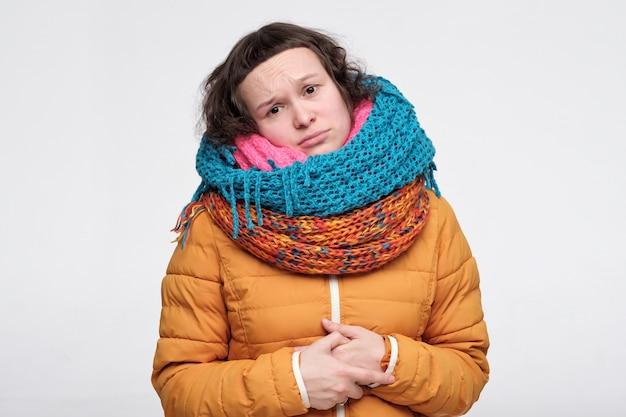 Jeune femme en plusieurs écharpes n'aime pas l'heure d'hiver