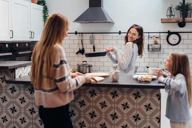 Une jeune femme avec une poêle à frire nourrit son amie et sa fille.