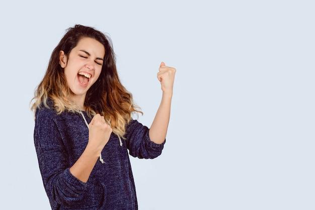Jeune femme avec des poings serrés et des cris oui.