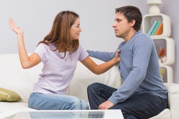 Jeune femme sur le point de gifler l'homme dans le salon à la maison