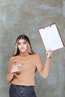 Jeune femme pointant sur un bloc-notes vide sur une pierre