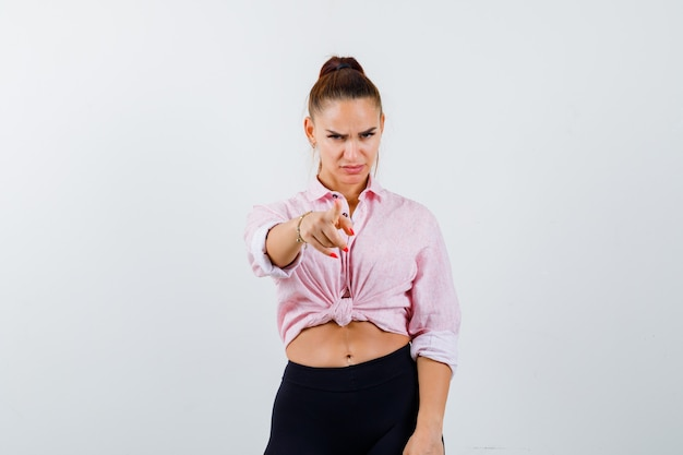 Jeune femme pointant la caméra en chemise, pantalon et à la sombre. vue de face.