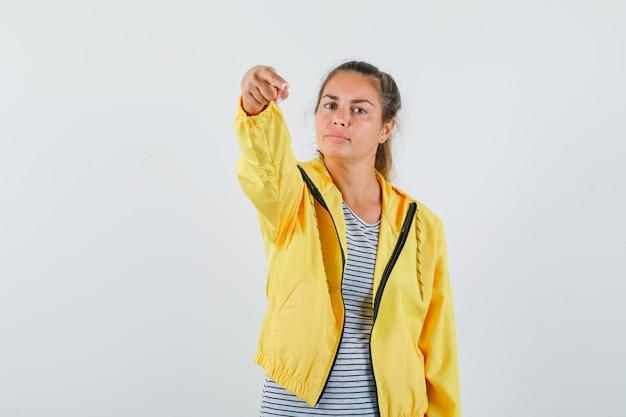 Jeune femme pointant la caméra en t-shirt, veste et à la vue de face, confiant.