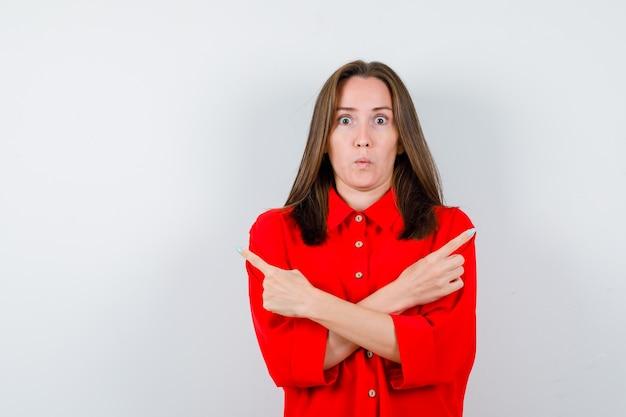 Jeune femme pointant de côté avec les bras croisés en blouse rouge et l'air choqué, vue de face.