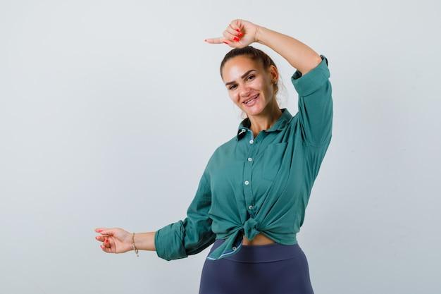 Jeune femme pointant de côté en chemise verte et ayant l'air joyeuse. vue de face.