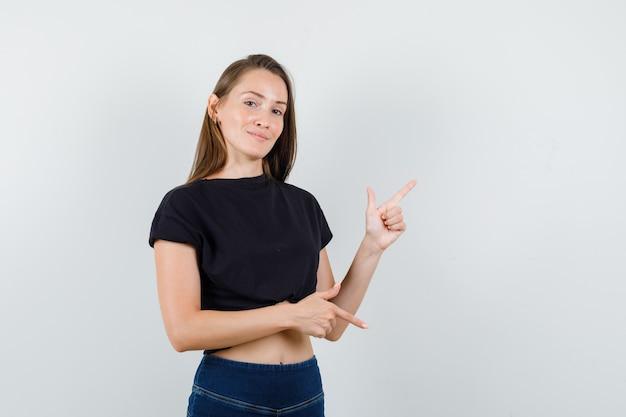 Jeune femme pointant de côté en chemisier noir et à la belle.