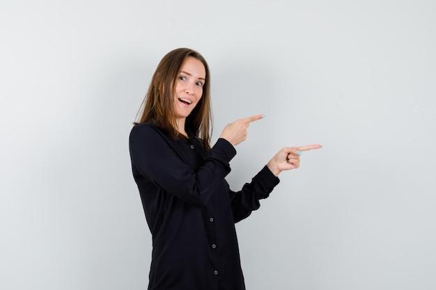 Jeune femme pointant de côté et à la gaieté