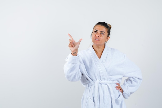 Jeune femme pointant de côté en peignoir et à la confiance