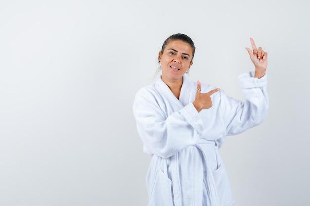 Jeune femme pointant de côté en peignoir et à heureux