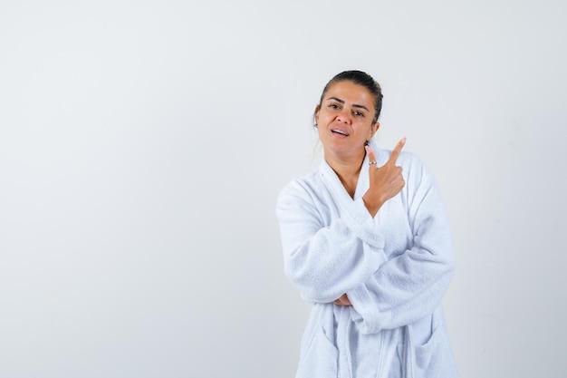 Jeune femme pointant de côté en peignoir et à la joyeuse