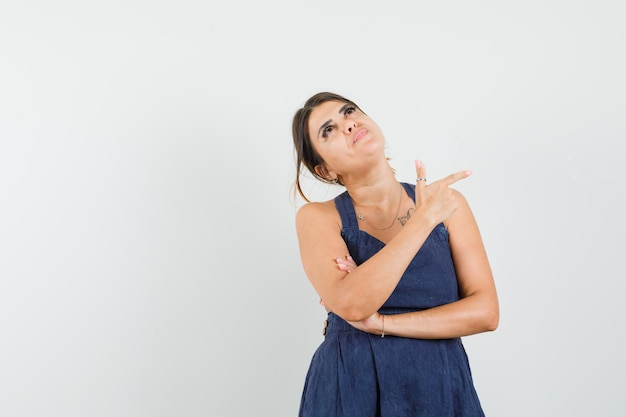 Jeune femme pointant sur le côté, regardant en robe et semblant concentrée