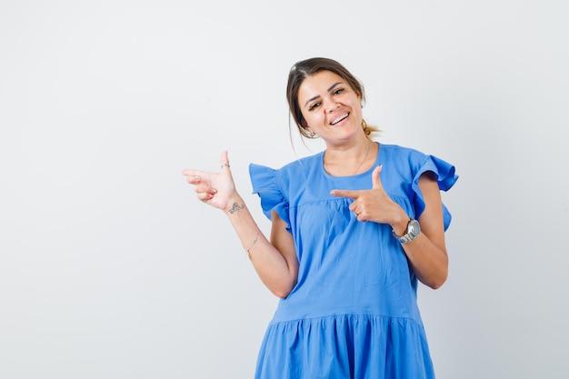 Jeune femme pointant sur le côté en robe bleue et à la gaieté