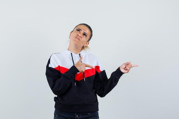 Jeune femme pointant de côté en sweat-shirt coloré et à la recherche têtue. vue de face.