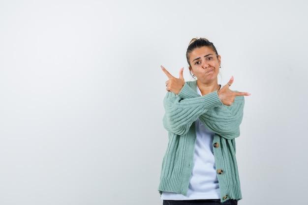 Jeune femme pointant de côté en t-shirt, veste et à la joyeuse