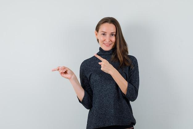 Jeune femme pointant de côté et vers le haut en chemise et à l'optimiste