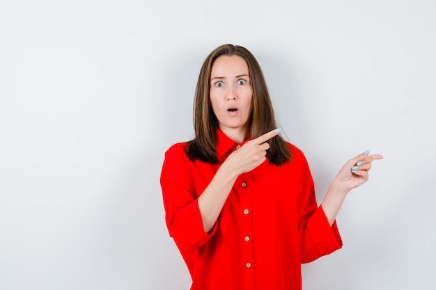 Jeune femme pointant sur le côté et vers le haut en chemisier rouge et l'air choqué, vue de face.