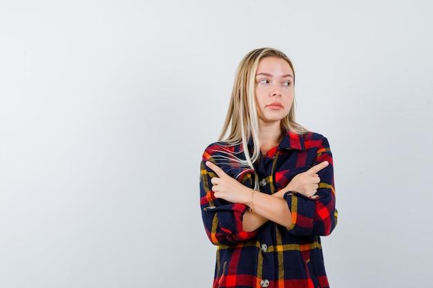 Jeune femme pointant les côtés croisés en chemise à carreaux et regardant hésitante. vue de face.
