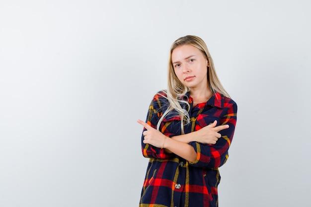 Jeune femme pointant des deux côtés en chemise à carreaux et regardant hésitante. vue de face.