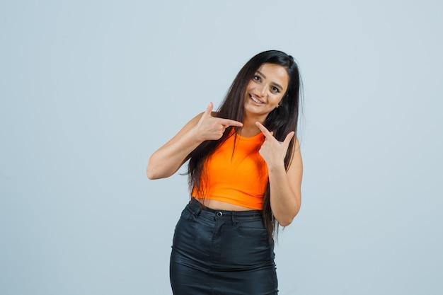 Jeune femme pointant les deux côtés en maillot, mini jupe et à la vue de face, heureux.