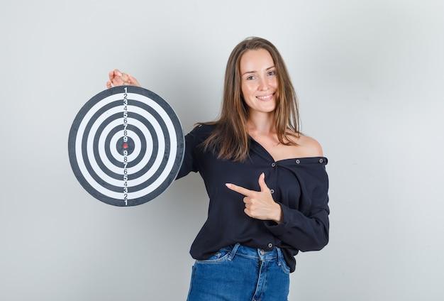 Jeune femme pointant le doigt au jeu de fléchettes en chemise noire, short en jean et à la joyeuse