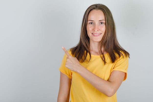 Jeune femme pointant le doigt vers l'arrière en t-shirt jaune et à la joyeuse