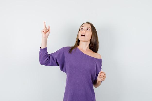 Jeune femme pointant le doigt vers le haut en chemise violette et regardant focalisée, vue de face.