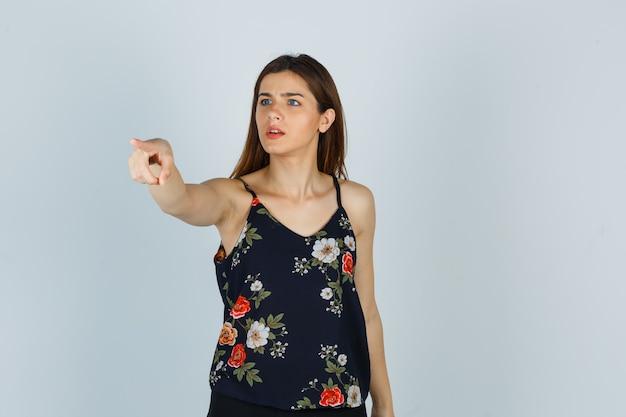 Jeune femme pointant du doigt en blouse et à la perplexité, vue de face.