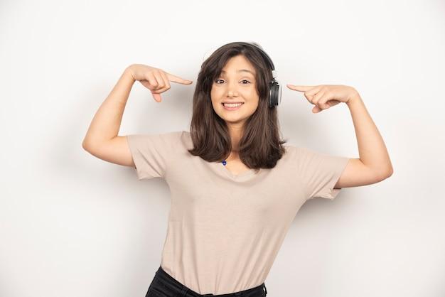 Jeune femme pointant sur les écouteurs sur fond blanc.