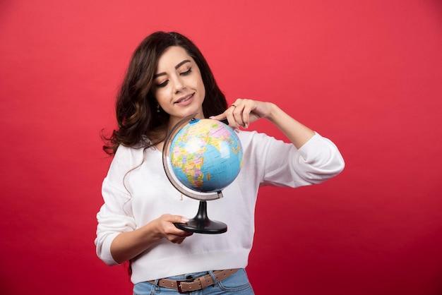 Jeune femme pointant sur globe sur fond rouge. photo de haute qualité