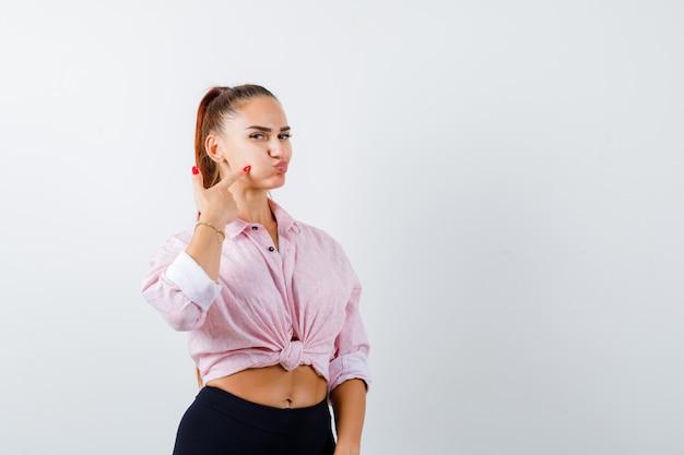 Jeune femme pointant sur la joue soufflée en chemise décontractée et à la jolie vue de face.