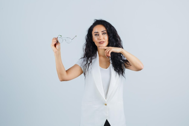Jeune femme pointant sur des lunettes en t-shirt blanc, veste et l'air confiant, vue de face.