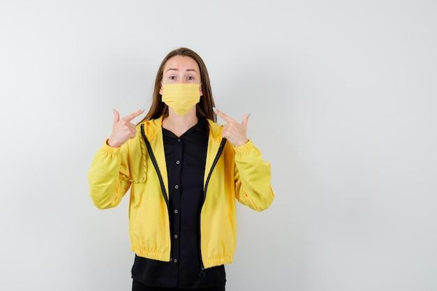 Jeune femme pointant sur masque avec index