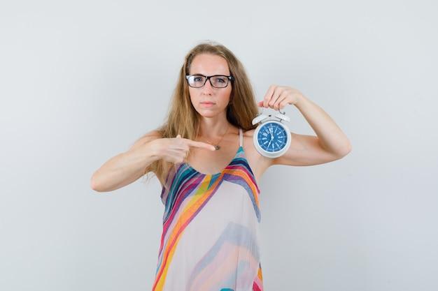 Jeune femme pointant sur le réveil en robe d'été et à la ponctualité.