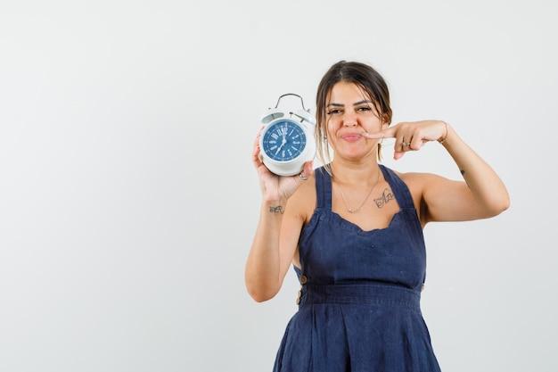Jeune femme pointant sur réveil en robe et à la ponctualité