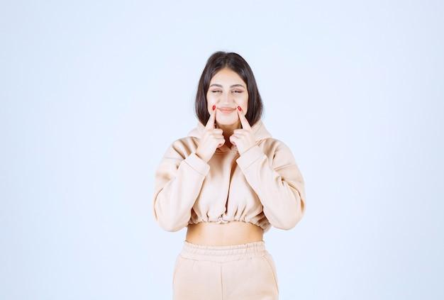 Jeune femme pointant sa bouche et signifiant son sourire ou son hygiène bucco-dentaire