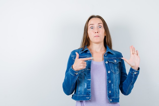 Jeune femme pointant sur sa main levée en t-shirt, veste et l'air perplexe. vue de face.