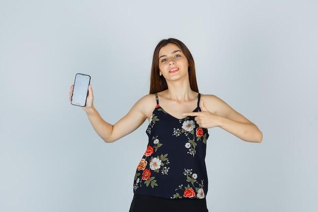 Jeune femme pointant sur smartphone en chemisier et l'air confiant, vue de face.