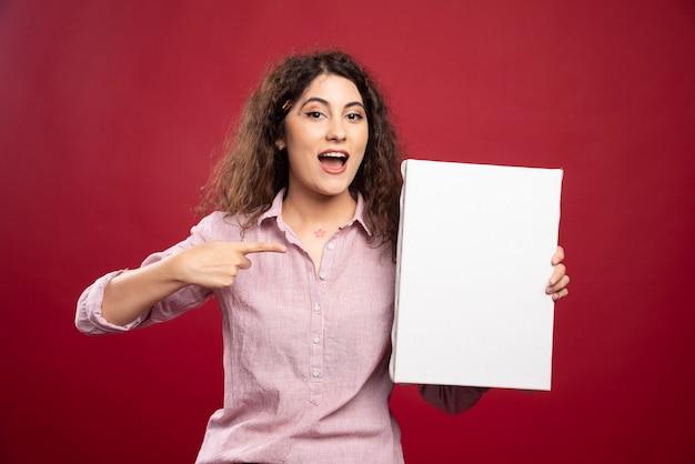 Jeune femme pointant sur une toile vide.