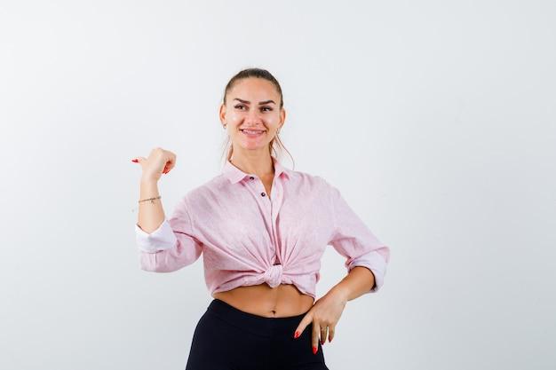 Jeune femme pointant vers l'arrière avec le pouce en chemise, pantalon et à la joyeuse. vue de face.