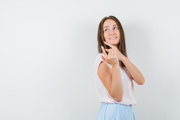 Jeune femme pointant vers l'arrière en t-shirt, jupe et à la recherche d'espoir.