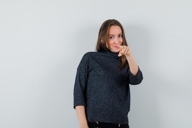 Jeune femme pointant vers l'avant en chemise et à l'optimiste
