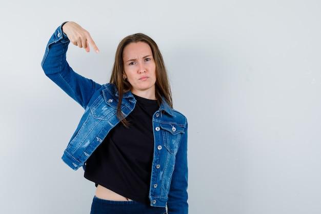 Jeune femme pointant vers le bas en blouse, veste et l'air confiant, vue de face.
