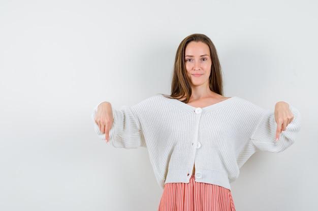 Jeune femme pointant vers le bas en cardigan et jupe à la confiance isolée