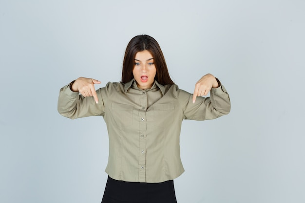 Jeune femme pointant vers le bas en chemise, jupe et à la surprise