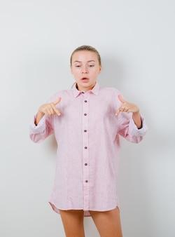 Jeune femme pointant vers le bas en chemise rose et à la peur
