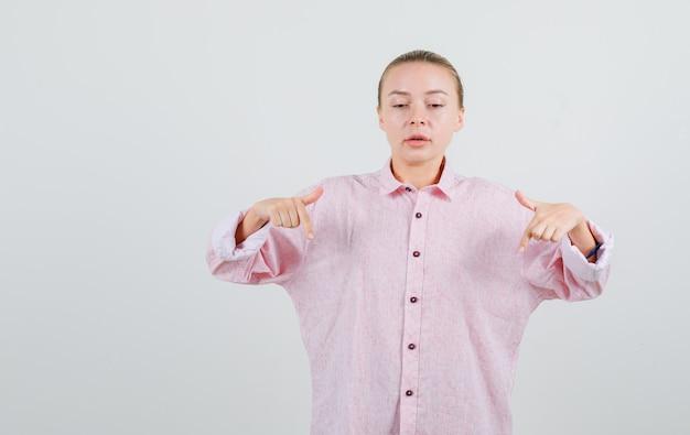 Jeune femme pointant vers le bas en chemise rose et à la recherche concentrée